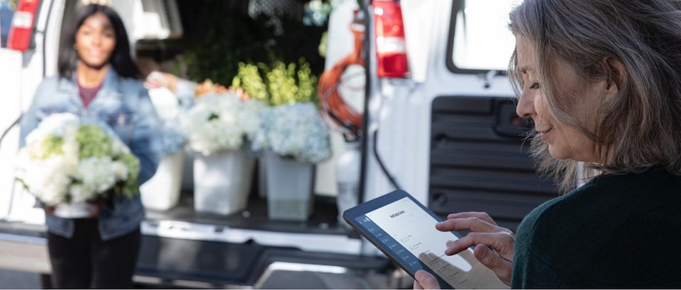 Woman using OnStar data services on tablet during flower delivery