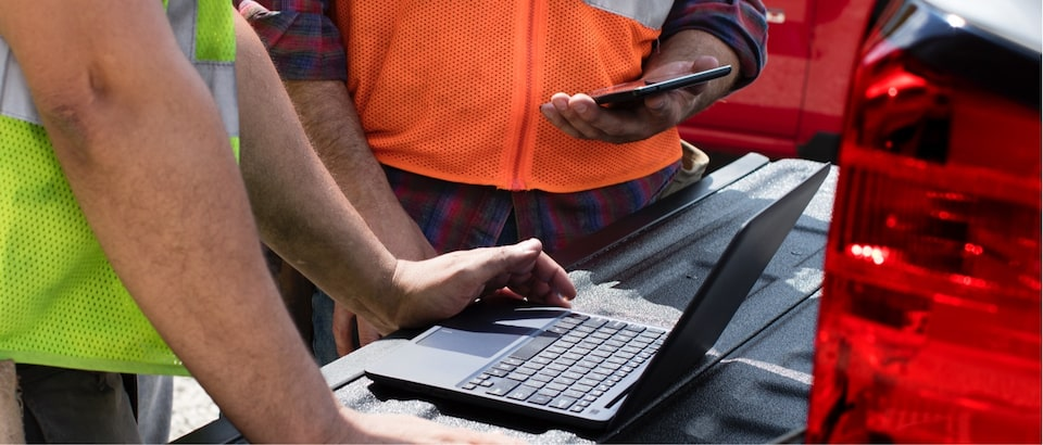 Men using 4G LTE Wi-Fi on laptop at worksite