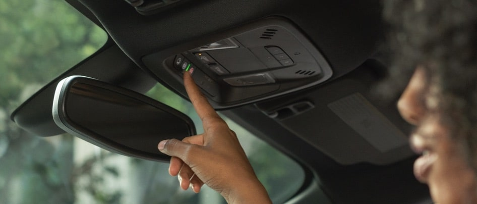 Woman pushing OnStar button in vehicle